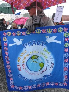 My husband and partner at a peace rally using one of our peace wall hangings.